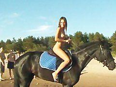 Nackte Frau beim Pferde reiten
